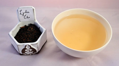 A side by side comparison of Lychee Cha leaves and steeped tea. On the left, the leaves are black and dark brown. On the right, the steeped tea is a vibrant yellow.