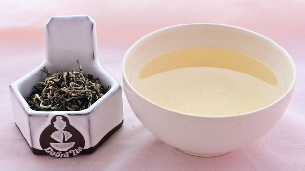 A side-by-side comparison of Magnolia Mao Jian leaves and steeped tea. On the left, the leaves are twisted and range in color from light green to dark green. On the right, the steeped tea is a pale yellow.