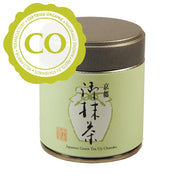 "A small metal canister about the size of a human palm. It has a brown lid that can lift off and a pale green body. It on the body is an image of a jar with Japanese characters and a red production stamp. It says ""Japanese Green Tea Uji Chanoka"" in English below. A sticker labels the tea as Certified Organic."
