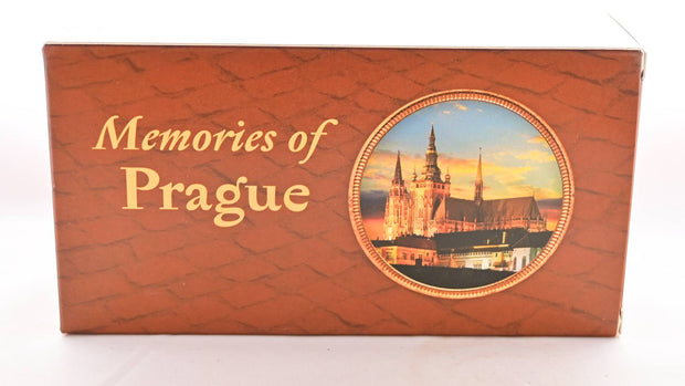 "The Memories of Prague paper box is brick-red with a shingled pattern across it. Inside a circle toward the right, a magnificent cathedral is featured against a sunset. Text reads: ""Memories of Prague."""