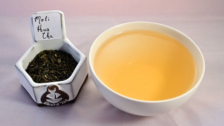 A combination of leaves and a steeped tea cup. The leaves are dark green and appear slightly crumbled. The steeped tea is a red-caramel color.