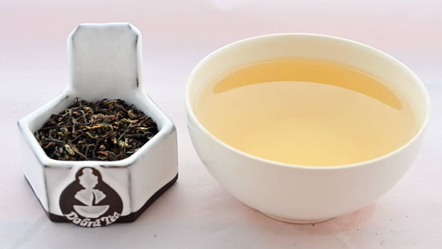 A side-by-side comparison of Nepal Illam leaves and steeped tea. On the left, the leaves apepar predominantly black, with a few shades of green and orange scattered throughout. On the right, the steeped liquid is a golden yellow color.