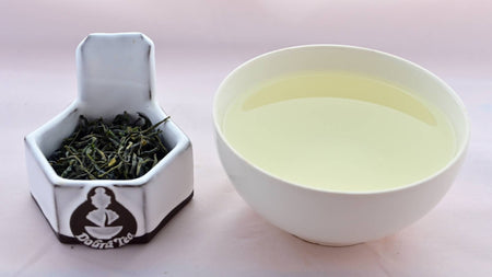A side-by-side comparison of Nok Cha leaves and steeped tea. On the left, the leaves are medium-length and narrow, and appear to be a dark green color. On the right, the steeped liquid is a pale green.