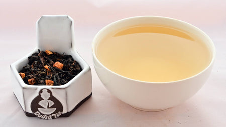 A side-by-side comparison of Plum Tea leaves and steeped tea. On the left, black tea leaves encircle nuggets of orange-colored dried plum. On the right, the liquid is a soft yellow color.