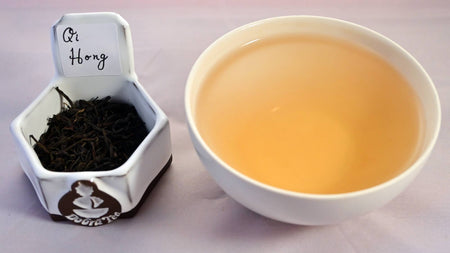 A side-by-side comparison of Qi Hong Mao Feng leaves and steeped tea. On the left, the leaves are small, tightly curled, and black. On the right, the steeped liquid is a soft orange.