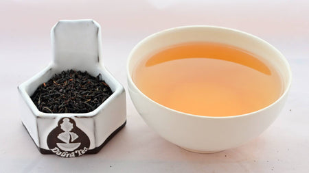 A side-by-side comparison of Rwandan Black leaves and steeped tea. On the left, teh tea leaves are small, tightly packed, and black. On the right, the liquid is a reddish brown mix.