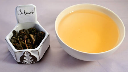 A side-by-side comparison of Sakuracha leaves and a cup of brewed tea. The leaves are whole and curled in on themselves. The steeped liquid is vibrant yellow.