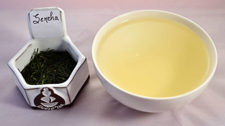 A picture of tea leaves  on the left with steeped tea on the right. The tea leaves are deep green, short, and needle-thin. The tea is pale yellow.