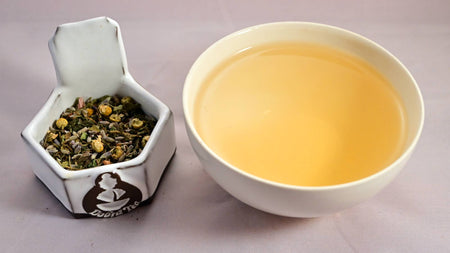 A side-by-side comparison of the Serenitea blend and steeped tisane. On the left, the herbal blend prominently features lavender, chamomile, and tulsi. On the right, the steeped tisane is light orange.