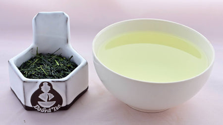 A side-by-side comparison of Shincha leaves and steeped tea. On the left, the leaves are predominantly dark green, long, flat, and narrow. On the right, the steeped liquid is a pale green.