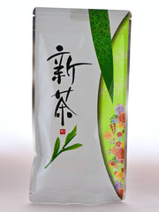 The Shincha package is mainly white, with green patterning on the right side. Inside one of the green semi-circles is a group of red and yellow flowers. On the left size of the plastic package are Japanese letters followed by a tea leaf.