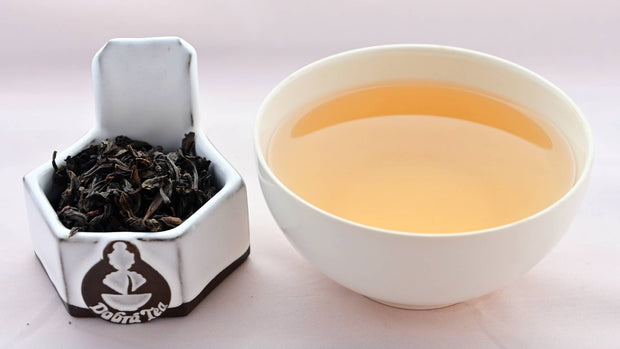 A side-by-side comparison of Wuyi Shan Shui Xian leaves and steeped tea. On the left, the leaves are dark brown and swirled into loose spirals. On the right, the steeped liquid is pale orange.
