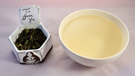A side-by-side comparison of Tie Guan Yin leaves and steeped tea. The leaves are a light green, and scrunched together into small, wrinkled pebbles. On the right, the steeped liquid is pale peach.