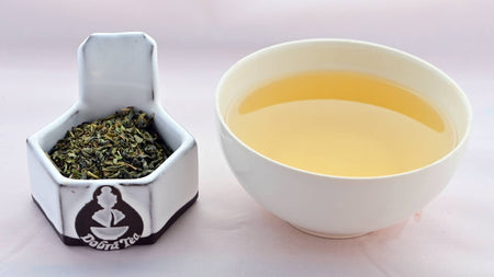 A side-by-side comparison of Touareg leaves and steeped tea. On the left, the leaves are a mixture of flat bright-green flakes and rounded, dark green pebbles. On the right, the steeped liquid is a soft yellow.