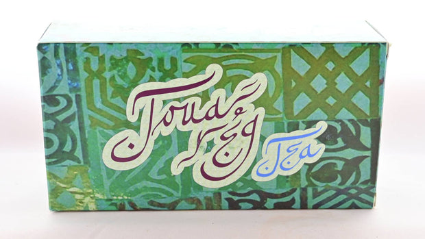 "The Touareg box is predominantly green, with Moroccan designs tiled across it. Curly lettering in brown and blue reads ""Touareg Tea""."
