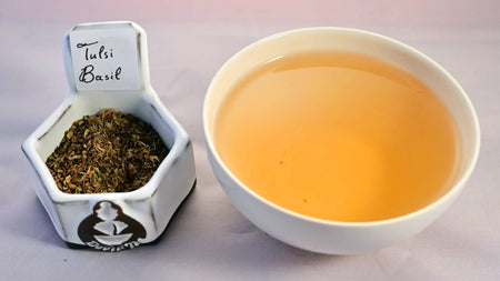 A side-by-side comparison of the tulsi herb and steeped tisane. On the left, the tulsi leaves are small, dust-like and range in color from green to brown. On the right, the steeped tisane is a soft orange color.