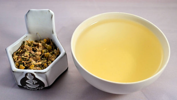 A side-by-side comparison of the Tummy Tamer blend and steeped tisane. On the left, the herbal blend prominently features chamomile and ginger root. On the right, the steeped tisane is a warm yellow color.