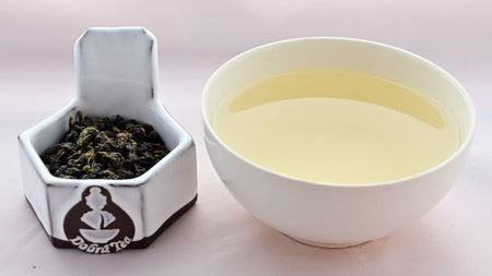 A side-by-side comparison of Tung Ting leaves and steeped tea. On the left, the leaves are dark green and have been scrunched and rolled together into pebble-like shapes. On the right, the steeped liquid is a pale yellow.
