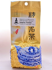 The Tung Ting package is predominantly gold, with an ornate blue teapot on the bottom portion. The top two thirds of the packet is smooth, and the bottom third bulges out indicative of vacuum-sealing around the pebble-shaped leaves. There is a Dobra identification sticker on it, obscuring some Chinese lettering.