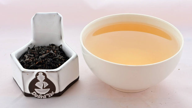 A side-by-side comparison of Vanilla Tea leaves and steeped tea. On the left, the tea leaves are black and slightly broken. On the right, the steeped liquid is a caramel color.