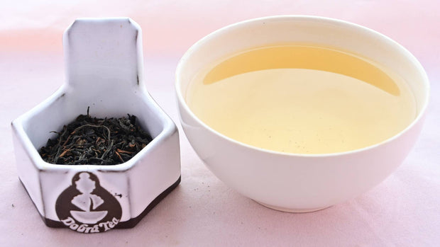 A side-by-side comparison of Wooricha leave and steeped tea. On the left, the leaves are narrow and curving, and a dark black color. On the right, the steeped tea is a rich yellow color.