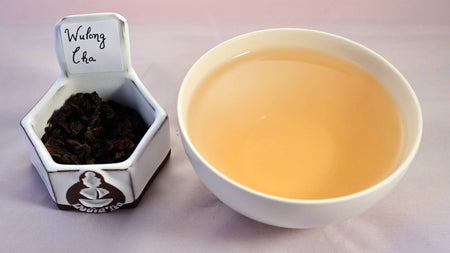 A side-by-side comparison of Wu Long Cha leaves and steeped tea. On the left, the leaves are dark brown and curled into tight, wrinkled pellets. On the right, the steeped liquid is a warm orange.