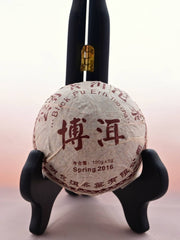 "The Xiang Wei Tuo Cha dome rests in a black book holder. It is wrapped in white tissue paper with red designs of flowers in the background. Chinese letters circle the outside, with English translations inside reading: ""Black Pu Erh Tuo Cha. Spring 2016. 100 grams."""