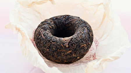 The Xiang Wei Tuo Cha dome rests upside down against its creme tissue paper wrapper. The leaves curl toward the hollowed inside of the dome, and range in color from black to dark orange.