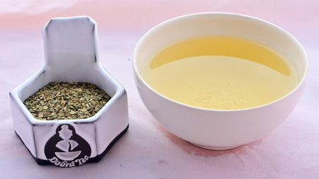 A side-by-side comparison of the dried Yerba Mate herb and steeped tisane. On the left, the leaves are small, flat, and relatively circular. They range in color from pale brown to green-brown. On the right, the steeped tisane is a deep yellow.