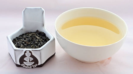 A side-by-side comparison of Zhu Cha leaves and steeped tea. On the left, the leaves are dark green, and resemble small, smooth pellets. On the right, the steeped liquid is a soft gold.