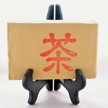The Zhuan Cha tea brick is wrapped in brown paper and resting in a black book stand. On the front is a single Chinese character stamped in red ink.