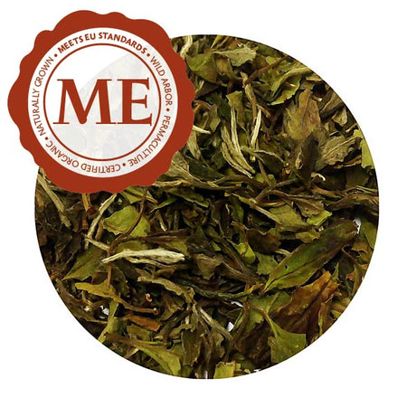 A close up of tea leaves. Most are green, with a slight brown tint. They are crisp and brittle. There is a Meets EU Standards label in the top left.