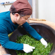 An image captures the pan-roasting step of Nok Cha processing. The processor is in a blue shirt, and leans over a wok-style pan while swirling their hand through vibrant green leaves.