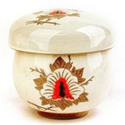 A close-up of the traditional Nok Cha drinking vessel, a single-serving cup with removable filter. This one has a cream base color, with leaf and flower designs in brown and red.