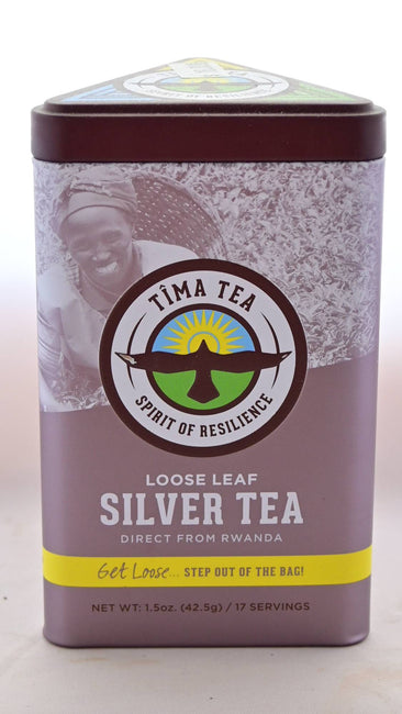 "A triangular silver tea tin holds Silver Rwandan tea. At the top is an image of a tea-picker smiling into the camera with a basket on their back. In the center, a logo featuring a bird with wings spread flying upward toward the sun is surrounded by words ""Tima Tea. Spirit of Resilience."" Below, the tin features other descriptive messaging: ""Loose leaf silver tea direct from Rwanda. Get loose... step out of the bag! Net weight is 1.5 ounces or 17 servings."""