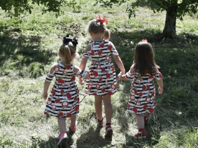 3 little girls at the orchard in cold shoulder dresses by Sydney So Sweet