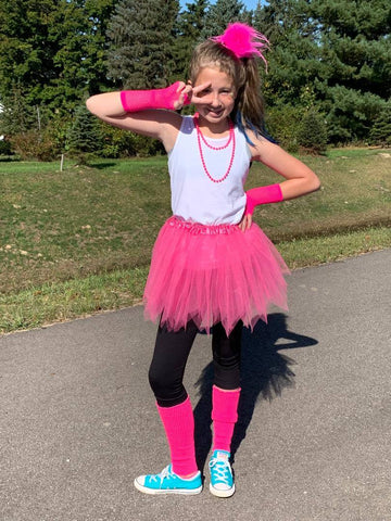School age girl wearing hot pink tutu.