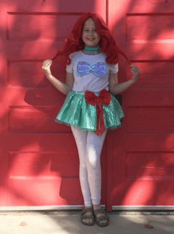 School age girl with red wig wearing aqua green tutu.