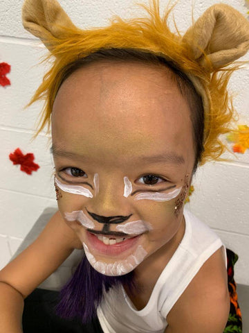 Smiling girl wearing lion face paint and headband.