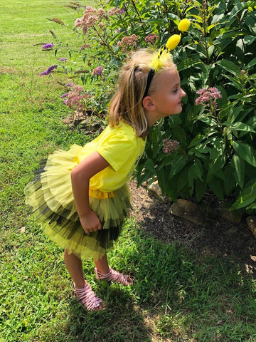 Blonde girl wearing black & yellow bee tutu costume is smelling a flower.