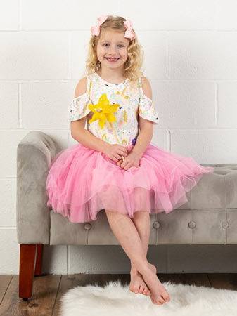 Little girl wearing pink birthday tutu set at party