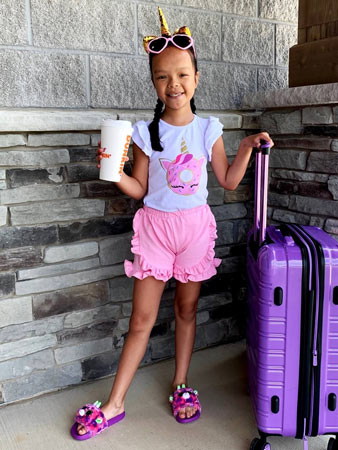 A little girl wears a donut unicorn shirt and holds a Dunkin Donuts cup and suitcase.
