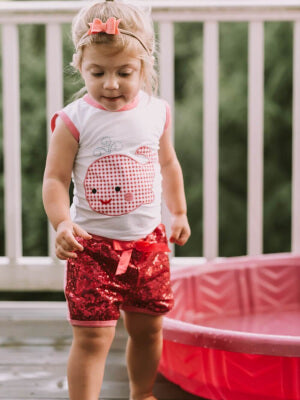 Little girl wearing red shorts & whale top.