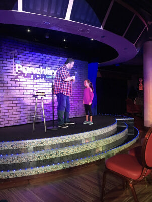 Ava on stage at comedy club on cruise spring break vacation