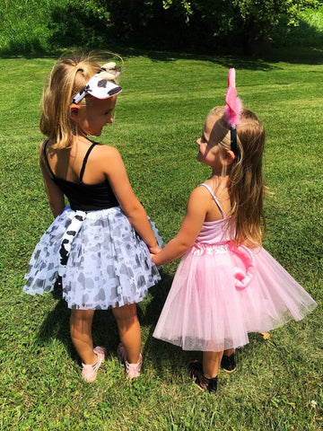 Two little girls holding hands wearing cow & pig themed tutu sets.