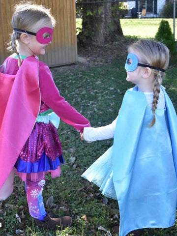 Two little girls holding hands and wearing princess superhero costumes with capes.