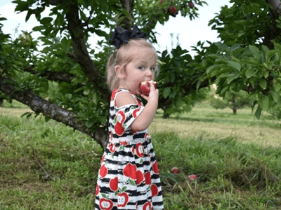 Girl eating apple in orchard in dress from Sydney So Sweet
