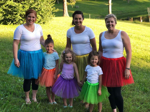 3 moms & 3 little girls outdoors wearing various colors of tutus.