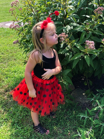 Little girl in ladybug themed tutu costume smelling flowers.