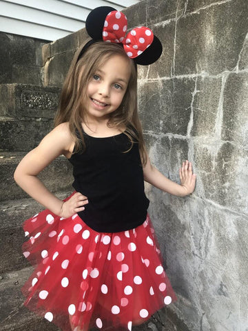Smiling girl wearing red polka dot Minnie Mouse tutu and headband.